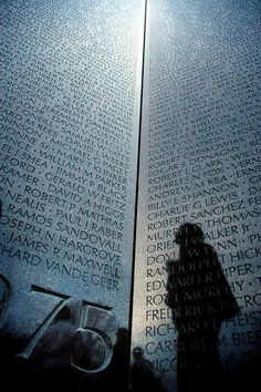 Vietnam Memorial. A woman solemnly stands at a corner of the Vietnam Memorial in Washington D.C. staring at the names of those who died in the war between 1974 and 1975.