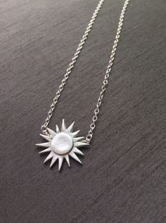 "Here comes the sun! Handcrafted in fine silver(.999%), this silver sun hangs at 16.5"" on a delicate sterling silver chain.($46)  #sunpendant #silverjewelry #modernjewelry"