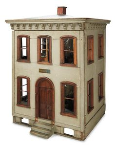 "Small Courtesies: 245 The 19th Century English Arnold J. Wilson Wooden Dollhouse and Furnishings  27"" (69 cm.) h. x 20"" x 18"". The thick-walled wooden two-story dollhouse has walnut framed windows and door,and paneled front double doors; there are four windows on each side. The front hinges open above three step stairs and basement crawl space with window cut outs. Two rooms are on each floor with arched door openings between,and the house is well-furnished with antique period…"