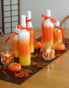 Candy Corn Centerpiece - Spray paint glass   bottles in candy corn pattern and tie with a ribbon. Add small white votives   surrounded by candy corn