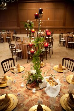 Unique centerpiece with cranberry candles, green vines, white oriental lilies, and grapes | villasiena.cc