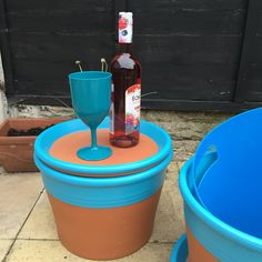 """Outdoor garden table made from plant pots. Large plant pots with saucers that fit on the top as lids (it can take a while to hunt out the right size pot and saucer at your local garden centre/DIY store). Ronseal Garden paint used to paint the pots (fantastic paint in some amazing colours - this took 3 coats to get this fabulous colour but dries very quickly and is water proof in 1 hour, suitable for wood, brick, metal etc... ). I used a """"cold drink"""" bucket from B&M stores in a similar blue"""