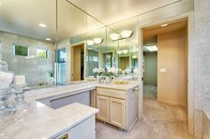 A wall of mirrors extending from the countertop to the ceiling visually expands the bathroom. A soothing neutral color palette and marble countertops create a fresh and clean contemporary design.