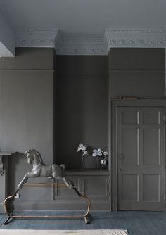 Farrow & Ball's Mole's Breath (Love the name!) grey. There is something beautiful in this space with the grey rocking horse and the somber cabinetry.
