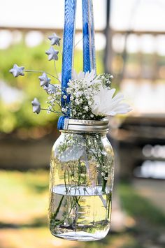mason jars are filled with baby's breath and daisies and hang by blue and silver ribbon