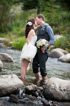 V3 Ranch, Breckenridge, Colorado, Mountain wedding, bride and groom, kissing in stream, barefoot, groom holding bouquet, stoney creek, rolled up pants, grey suit with vest