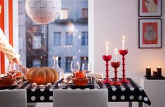 Ein Esstisch dekoriert für Halloween mit schwarzen und orangefarbenen Accessoires, u. a. HÅRFIN Kerzenständer/-halter in Rot