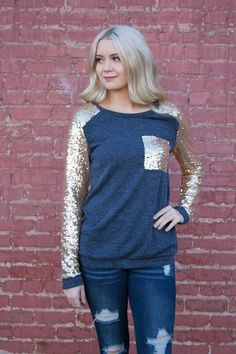 This top has the perfect amount of sparkle this holiday season! Whether it's to a holiday party or just out to dinner, you are sure to make a statement wherever you go. This top is also very versatile- leggings, jeans or even a skirt, whatever your style, this shirt will go!It has a perfect, flattering  fit that hits at the waist and features french terry lined sequin sleeves and pocket. This top is very soft and will also keep you warm- the feel of a sweatshirt, while  still loo...