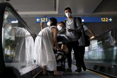 Passengers wearing masks to prevent contracting Middle East Respiratory Syndrome (MERS) ride on a travelator upon arrival at Incheon International Airport in Incheon, South Korea, June 2, 2015. South Korea on Tuesday reported its first two deaths from an outbreak of MERS that has infected 25 people in two weeks, as public alarm grew and officials scrambled to contain the outbreak. REUTERS/Kim Hong-Ji