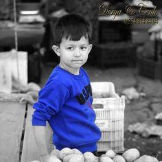 Pazar yerinde küçük bir pazarcı, babasına yardım ediyor belli ki..