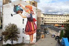 In Poland, Natalia Rak painted a new mural for the Folk on the Street 2013 event. Playing with ideas of scale, the clever piece features a girl watering a small plant or tree depending on your perspective and can be found on the side of the Institute of Chemistry building at the University of Bialystok.