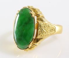 A regal antique green jade solitaire ring, prong set in 20Kt gold, Qing Dynasty, China circa 1820's - 1900's. The fine oval cabochon cut jadeite