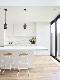This renovated heritage cottage hides a modern interior This white kitchen features two black glass statement pendant lights over the white marble kitchen island. Pale timber flooring runs throughout. White Kitchen Interior, White Marble Kitchen, Interior Modern, Home Decor Kitchen, Interior Design Kitchen, Home Design, Design Ideas, Kitchen Ideas, Modern White Kitchens