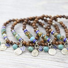 Charm bracelets are a great way to accessorize as well as carry something special and meaningful with you throughout the day. These 5 bracelets are made with a combination of gorgeous dark wood, lapis disk spacers, and glistening faceted Czech glass beads. Each bracelet features a set of charms from Nepal with their own design including: a lotus flower, sitting Buddha, a Hindu deity image, an elephant (or Ganesh), and the Star of David. Choose a charm that has special meaning to you, or collect Healing Bracelets, Crystal Bracelets, Charm Bracelets, Rustic Jewelry, Bohemian Jewelry, Jewelry Making Beads, Beaded Jewelry, Czech Glass Beads, Turquoise Bracelet