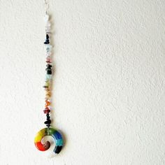 Chakra hanging piece made from gemstones and a handmade glass spiral. Message me for a custom order.