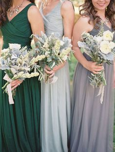 bridal party in bridesmaid dresses in emerald, pewter, and silver, holding white bouquets with dusty miller