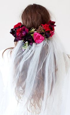 Boho bride's casual down hairstyle with low flower crown under veil