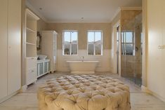 Master bathroom in new construction house with white vanity, freestanding tub and plush ottoman