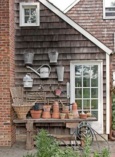 The owner of this New York home drafted a circa-1900 oak woodworker's table into service as a potting station, then hung vintage pails and watering cans on the exterior wall. NEXT: 11 Genius Ways to Organize With Pegboards   - CountryLiving.com