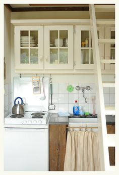 """A small stove top only set above either the counter-high refrigerator. To gain more counter space you could use a 24"""" or even an 18"""" sink. Apparently the microwave is being used rather  than a bake oven, although an oven could be on the opposite or adjacent wall set into storage area, or above a washer dryer combo unit."""