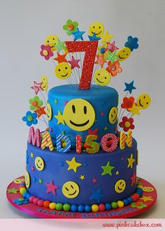 This surprise 7th birthday cake is just filled with happiness! The top of the cake includes stars, flower cutouts and yellow smiley faces. We used pearlize