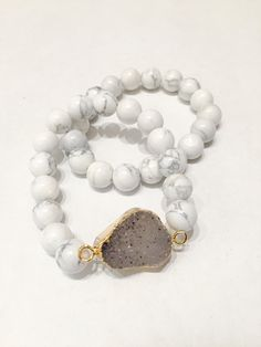 Stretchable bracelet set featuring white agate beads and one electroplated druzy stone in the center. Center druzy stones will vary in size and shape due to the nature of natural stones. Item #CHJST01