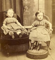 Post mortem picture.  Child on left has died and family takes a last picture to remember her. Very well accepted tradition in the 1800s.    memento mori, with sister