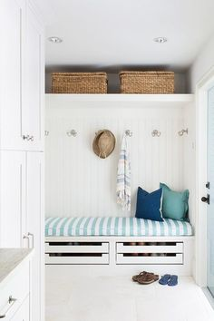 Gorgeous white beach bungalow mudroom with blue accents features two wicker baskets placed on a white shelf mounted against white beadboard trim above nickel coat hooks mounted over a white built-in bench fitted with stacked pull out shoe drawers and topped with a blue and white striped cushion.