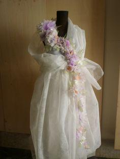 Il vestito bianco si carica di colore con la cintura di fiori di carta