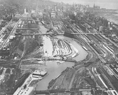 "Caption: ""This photograph was taken in 1929, a year before the river-straightening project was completed. The view is from the south toward downtown, and at this point is it possible to see both the river's old path and its new one. The photograph also makes evident how much of the real estate in this area was devoted to railroad tracks and yards.""
