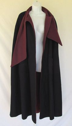 """front detail - open tie/collar detail - nurse (or other) cape/cloak inspiration - Vintage cloak/cape w/ attached scarf/tie collar - navy blue wool w/ burgundy-red wool facing  satin lining; double snap closure at the throat; Armholes at each side; large apron pockets at front - Label: Images  Accents; 80% wool, 20% nylon; Measurements: shoulders: 21""""; from top of armhole to other armhole: 54""""; length 45"""""""