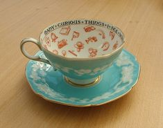 """Paragon Fortune Telling Teacup.  c.1932. Pale blue with raised cloud pattern and gilding. Inside it reads """"Many curious things I see when telling fortunes in your tea"""". There are also many interesting symbols to assist in the tea leaf reading process."""