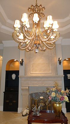 Large custom designed mantel, overmantel and hearth made of imported French limestone crafted by Stone Age Design in France with chimney lined in copper all the way to the top. Custom columns by Coral Light Stone over half wall. Large custom chandelier by Fine Arts Lamp Company ($8000)