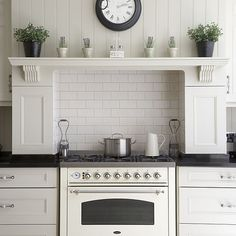 White kitchen tongue and groove wood panelled panelling walls fitted units alcove range cooker brick style ceramic tiles mantel mantelpiece plants vintage clock brass chandelier real home CH 03/2008 pub orig