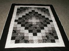 Trip around the world quilt done in black and white prints, throw size.