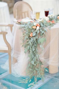 rose and eucalyptus garland on tulle covered sweetheart table @myweddingdotcom