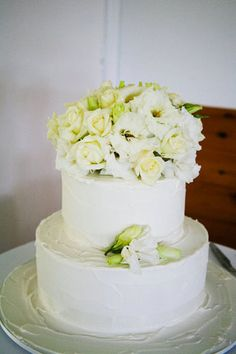 white 2 tier wedding cake with flowers. i would do it with fondant instead though.