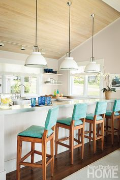 Beachy bar stools, wood ceiling and great light fixtures in this light kitchen.