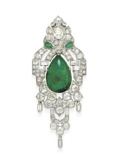 AN ART DECO DIAMOND AND EMERALD PENDANT BROOCH   Centering upon a pear-shaped cabochon emerald pendant, weighing approximately 21.53 carats, within an openwork old mine and baguette-cut diamond scalloped plaque of Oriental motif, enhanced at the top by two oval-cut emeralds and a larger old mine-cut diamond, suspending a fringe of hexagonal-cut diamonds, mounted in platinum, circa 1925
