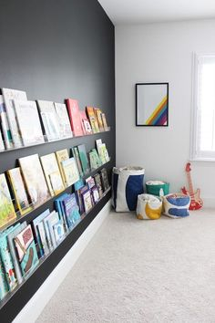 Major obsession with this black nursery wall filled with clear lucite shelves for baby colorful books. So fresh and modern!