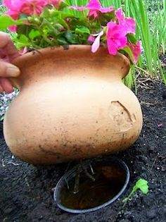 Make a hidden water reservoir for pots in the garden.When you pot up your flowers dangle a few 'wicks' (mop strings) out of the drainage holes. The wicks should be placed a few inches into the potting mix in your planter.