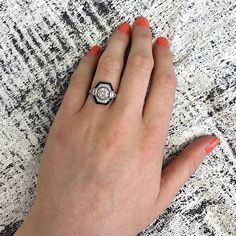 A beautiful and delicate handcrafted vintage engagement ring mounted in platinum and adorned with diamonds and onyx. The center diamond is an antique old European cut weighing approximately 1.15 carats, K color and VS2 clarity. The total approximate weight of the side diamonds is 0.28 carats....