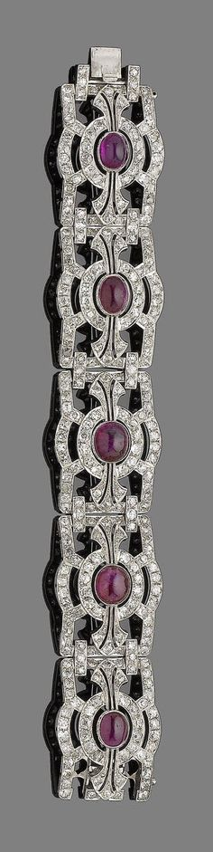 A ruby and diamond bracelet.  Composed of old brilliant and single-cut diamond openwork rectangular plaques, each collet-set to the centre with an oval cabochon ruby, millegrain-set throughout. Art Deco or Art Deco style.