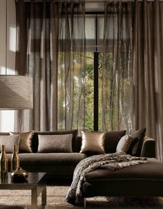 Sheer drapes over roller blinds in lounge. Exposed rod running wall to wall east to west. Walnut timber rod. Iron rings/loops.