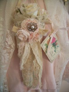 victorian tussie mussie - lace or crochet cone, adorned with vintage jewelry, buttons, tulle, and lace. ragamuffin roses made of hand dyed fabric strips hand-stitched and formed into a rose. Nice!