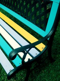 Wrought iron park bench painted in bright retro colours