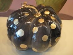 Small black pumpkin painted with gold dots.