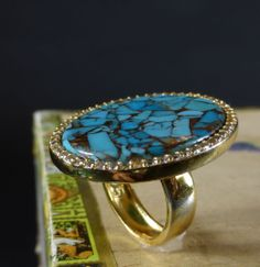 Spanish Queen Ring  Add a touch of natural color to any ensemble with this Turquoise ring. A large polished genuine Turquoise stone is set into a polished silver-tone ring.