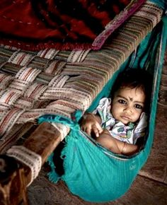 A baby is tied in a make shift crib attached to a cot.                                                                                                                                                                                 Mais