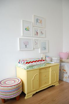 Pretty little girl's bedroom with crocheted stool and pale yellow chest of drawers. Love the pictures on the wall too.